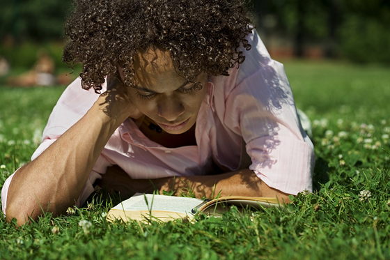 Person lying in grass and reading